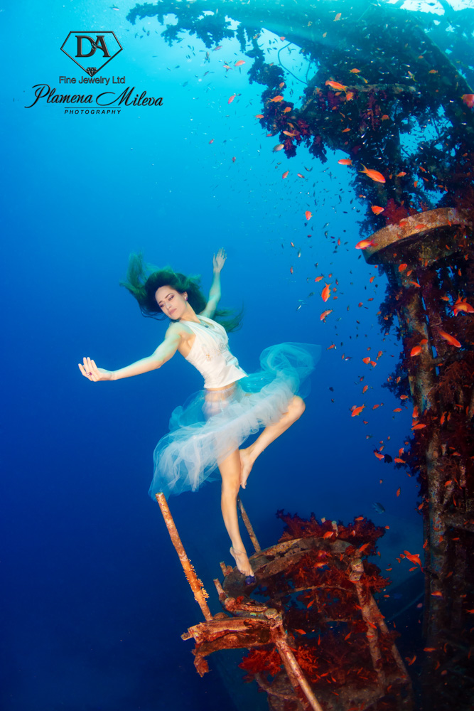 © Plamena Mileva | The incredible Satil Wreck has been an inspiration to many photographers. The intense red coral that covers the boat and the amount of small fish life that surrounds it, makes this shipwreck a beautiful sea life environment. I placed my dancer as if she was one of those dolls in a musical box, which as soon as you open attract you with its music and beauty. Can you remember these small ballet dancers which swivelled in a music box?  An old childhood memory that I relate to the beauty of this sunken wreck, surrounded with sea life. All the pictures I took in Eilat Red Sea Competition are carried out with: Canon 5D Mark III, Ikelite housing, 2 X 161 DS Ikelite strobes, Tokina 10-17mm f/3.5 -4.5 with trimmed hood