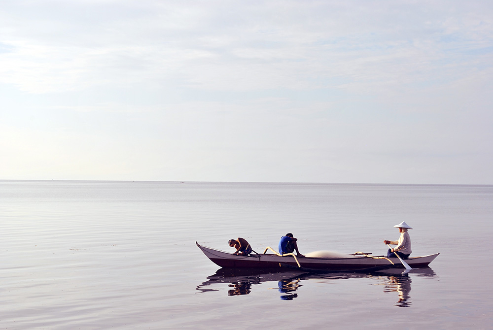 Three fishermen on a boat on the open sea.